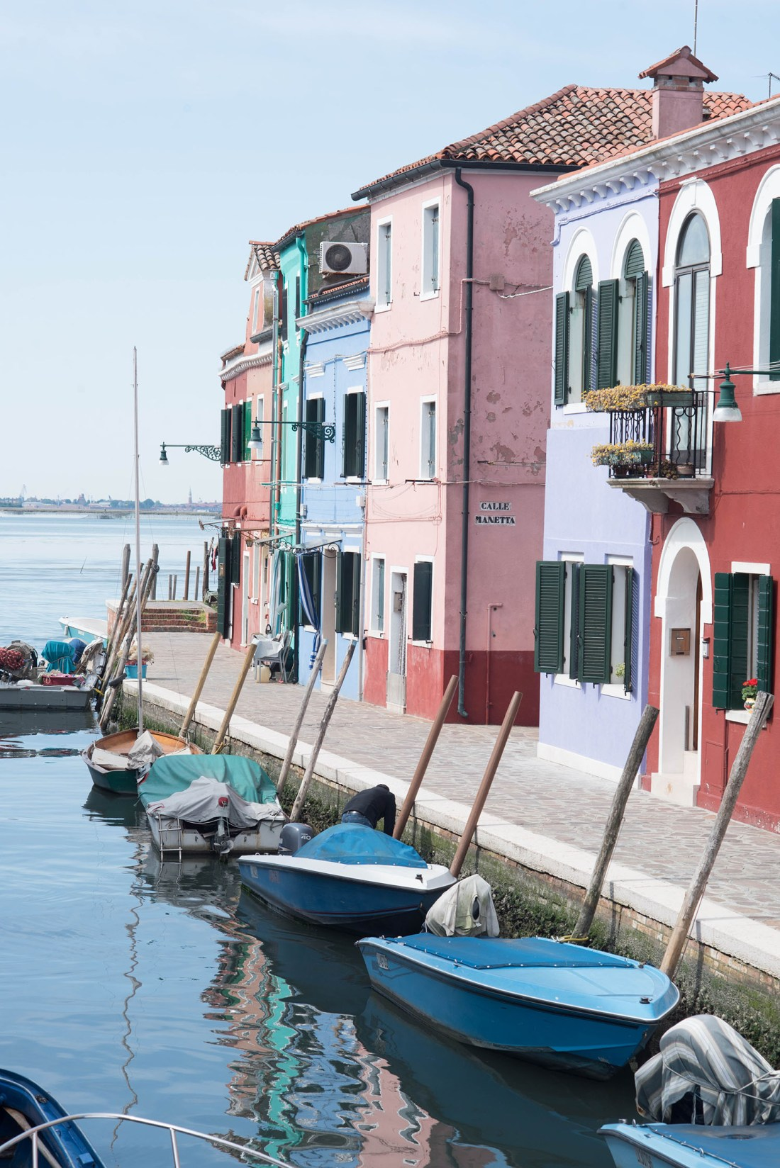 Pastel houses line the canal in Burano, Italy, captured by travel blogger Cee Fardoe of Coco & Vera