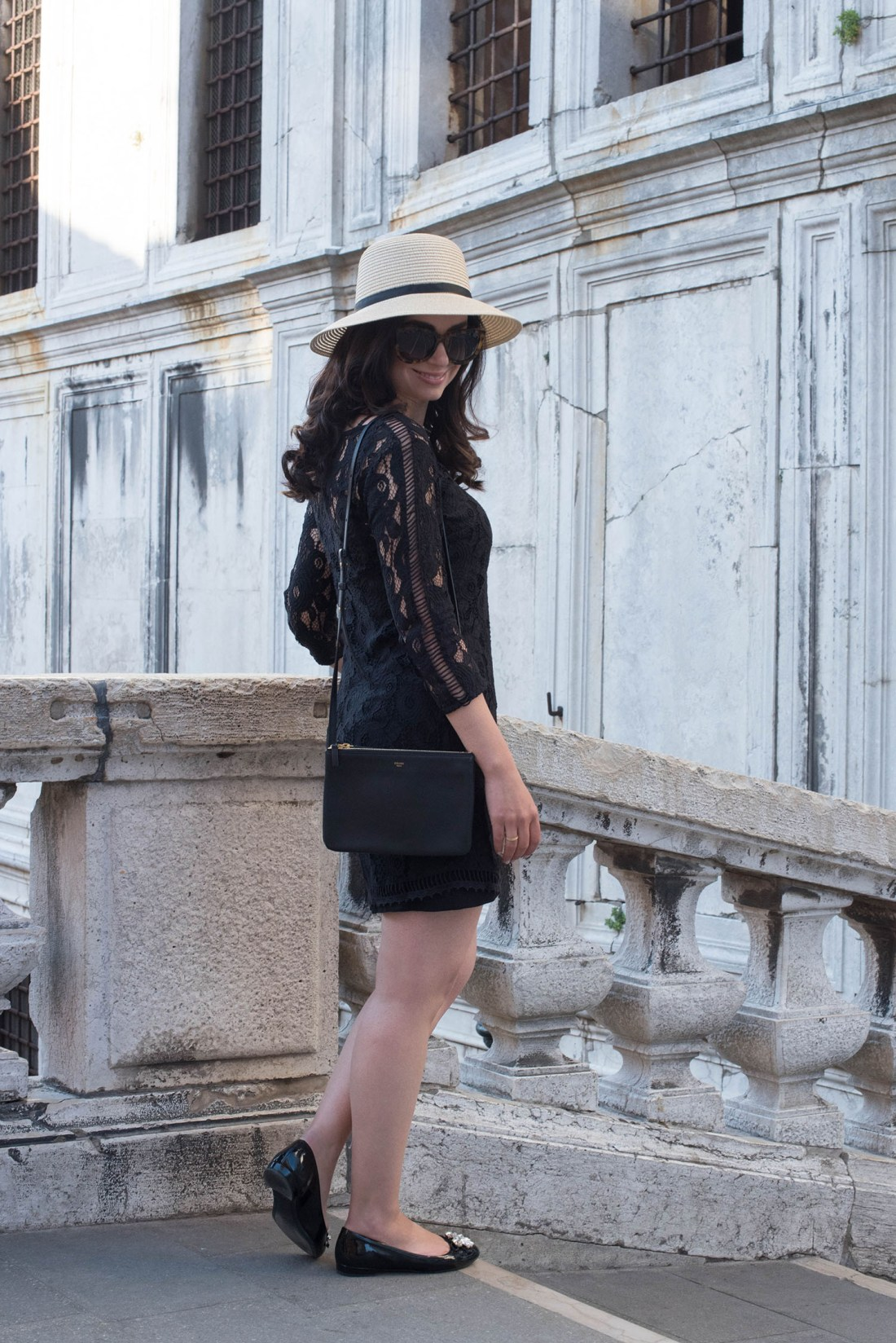 Winnipeg fashion blogger Cee Fardoe of Coco & Vera stands on a bridge in Venice wearing a Gentlefawn lace dress and carrying a Celine trio bag