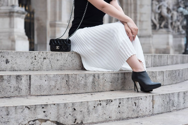 Outfit details on fashion blogger Cee Fardoe of Coco & Vera, including a Chanel extra mini patent handbag, Le Chateau ankle boots and Aritzia white pleated skirt