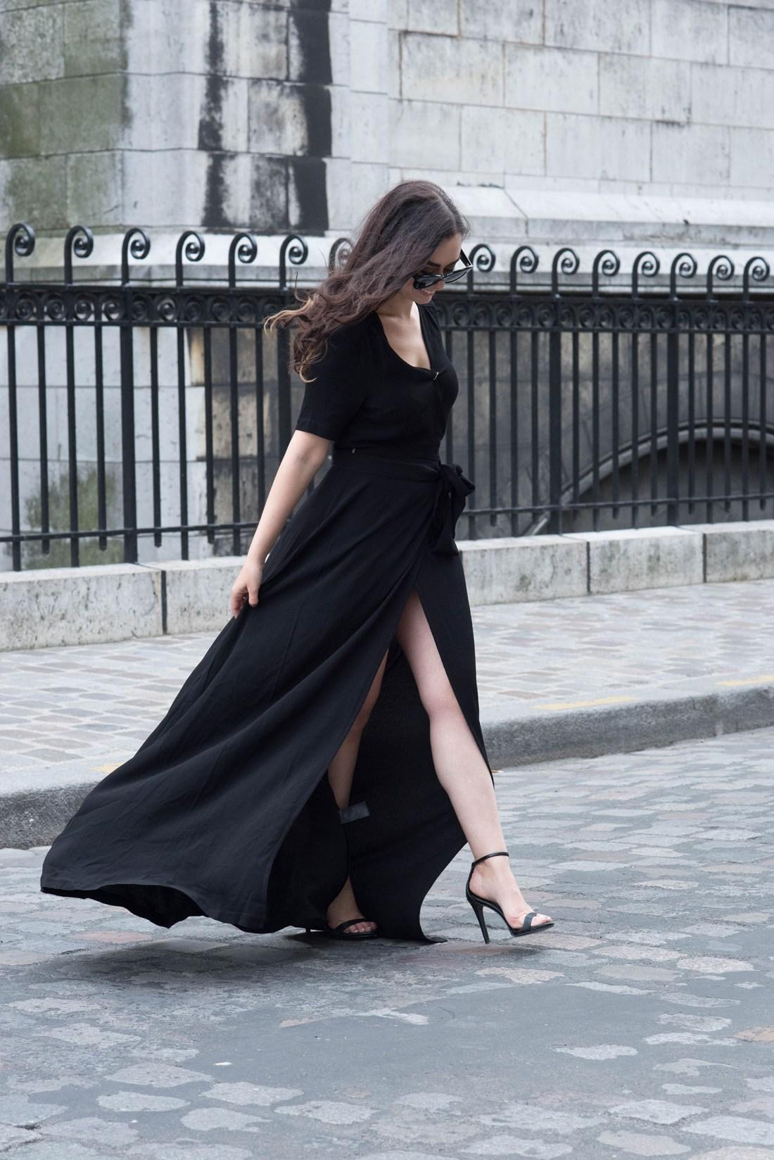 Fashion blogger Cee Fardoe of Coco & Vera walks in Montmartre wearing an Ivy & Oak black wrap dress and Steve Madden Stecy sandals