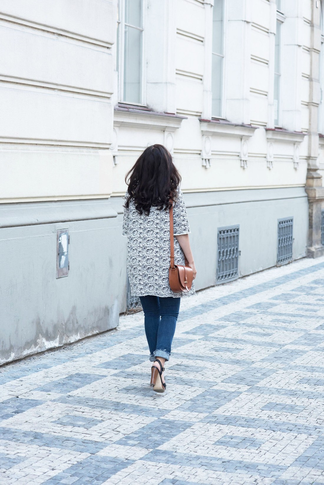 Fashion blogger Cee Fardoe of Coco & Vera walks down a Prague street wearing a Floriane Fosso coat and carrying a Sezane Claude bag