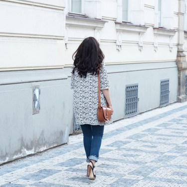 Fashion blogger Cee Fardoe of Coco & Vera walks down a Prague street wearing a Floriane Fosso coat and carrying a Sezane Claude bag