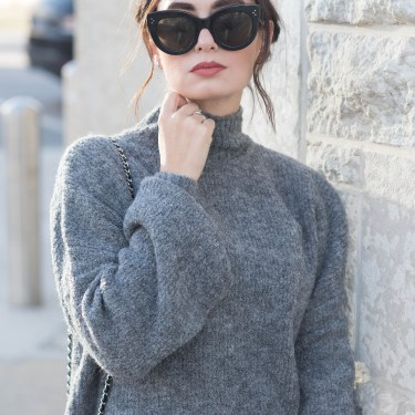 Portrait of Winnipeg fashion blogger Cee Fardoe of Coco & Vera wearing Celine Audrey sunglasses and a grey Lovers + Friends LA turtleneck sweater