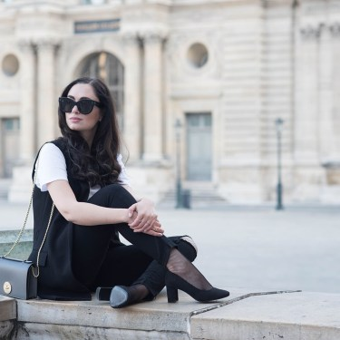 Winnipeg fashion blogger Cee Fardoe of Coco & Vera sits on the grounds of the Louvre wearing black Paige jeans and H&M block heels
