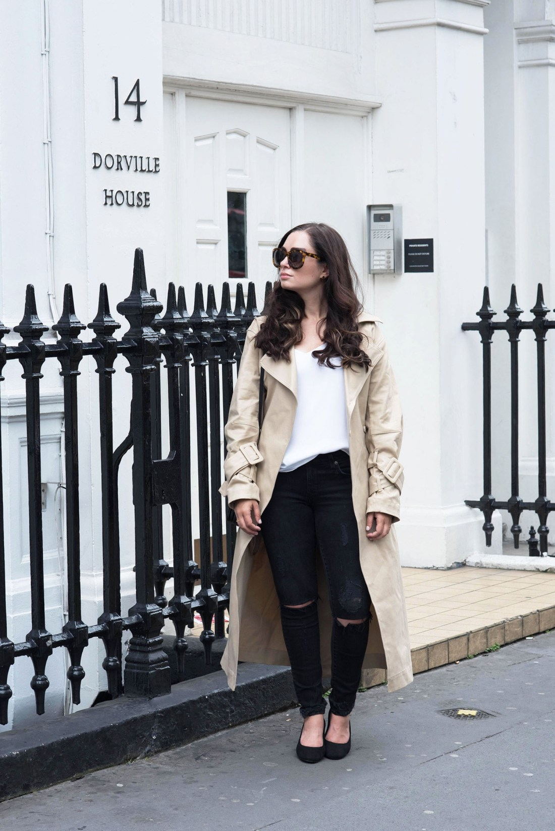 Fashion blogger Cee Fardoe of Coco & Vera stands at Dorville House in London wearing an H&M trench coat and Express Barcelona tank