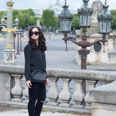 Fashion blogger Cee Fardoe of Coco & Vera stands at Place de la Concorde in Paris wearing an Everlane silk blouse and carrying an APF halfmoon bag