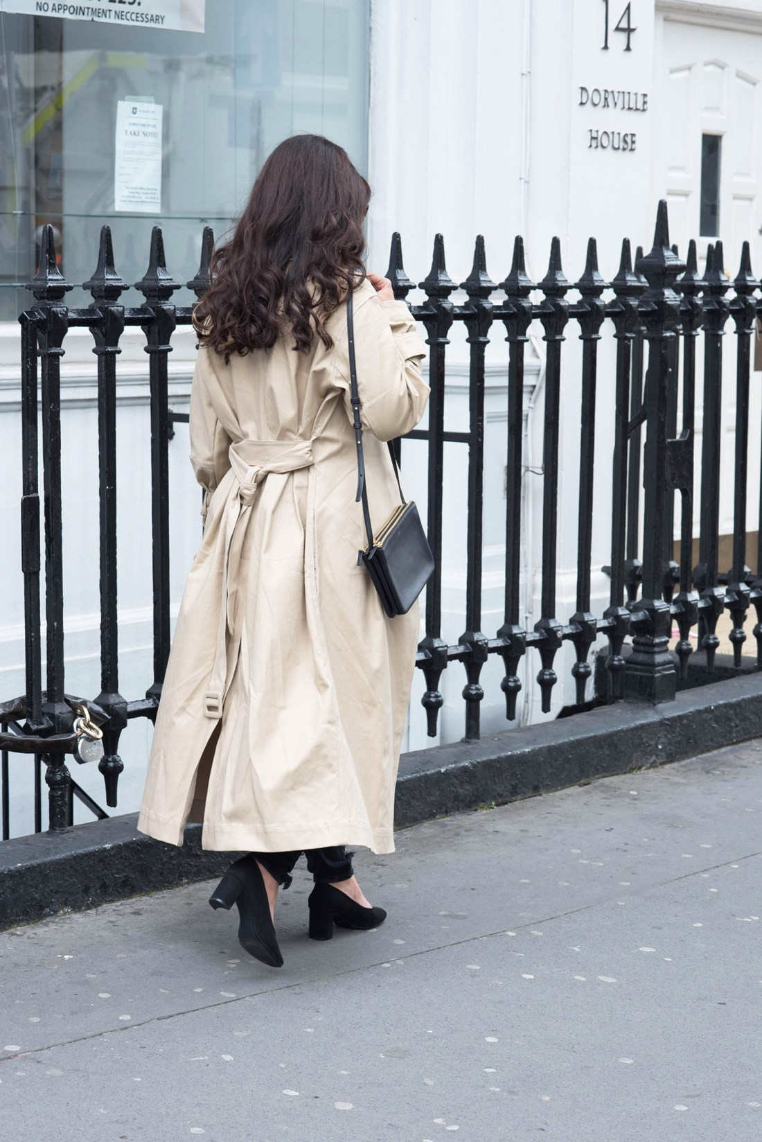 Fashion blogger Cee Fardoe of Coco & Vera walks in London wearing an H&M trench coat and carrying a Celine trio bag