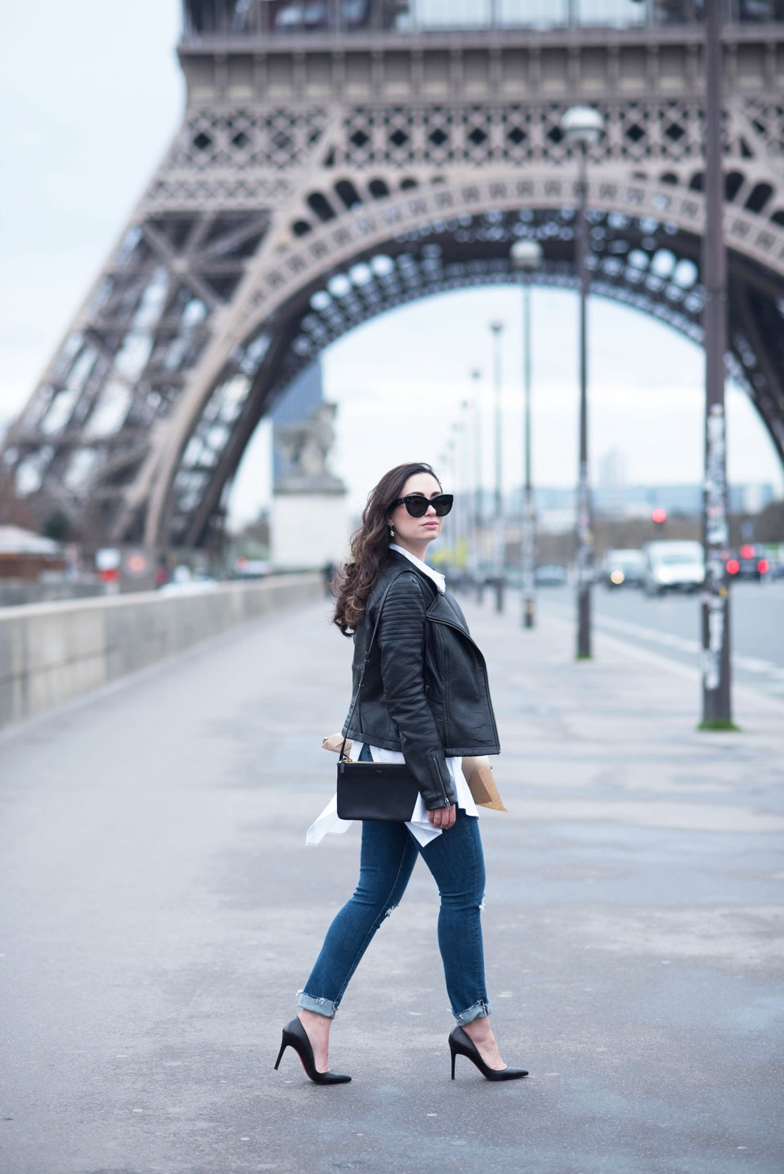 Canadian fashion blogger Cee Fardoe of Coco & Vera walks in front of the Eiffel Tower carrying a Celine trio bag and wearing Paige Hoxton jeans