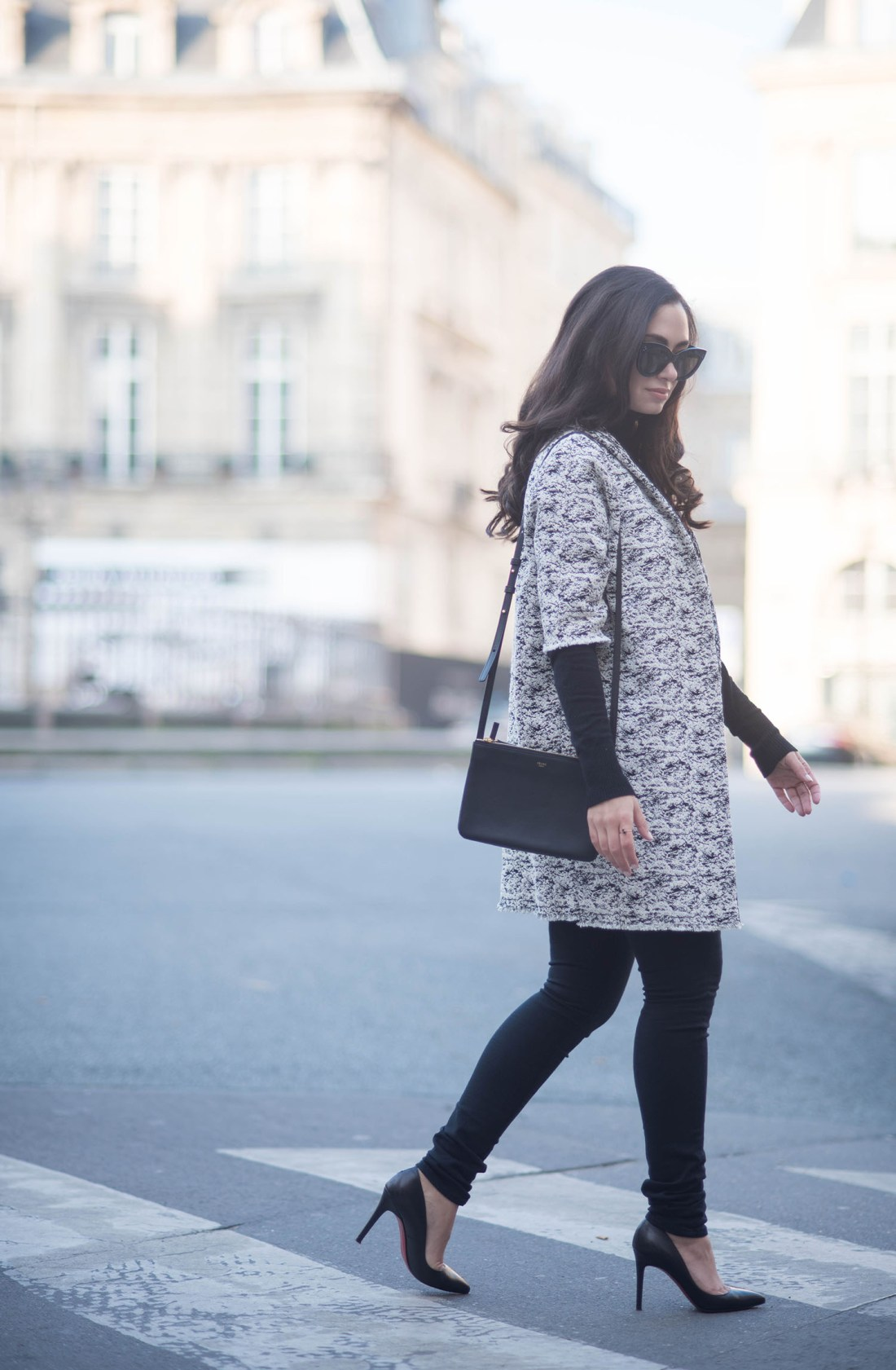 Fashion blogger Cee Fardoe of Coco & Vera crosses the street at Place des Victories in Paris carrying a Celine trio bag and wearing Mavi jeans