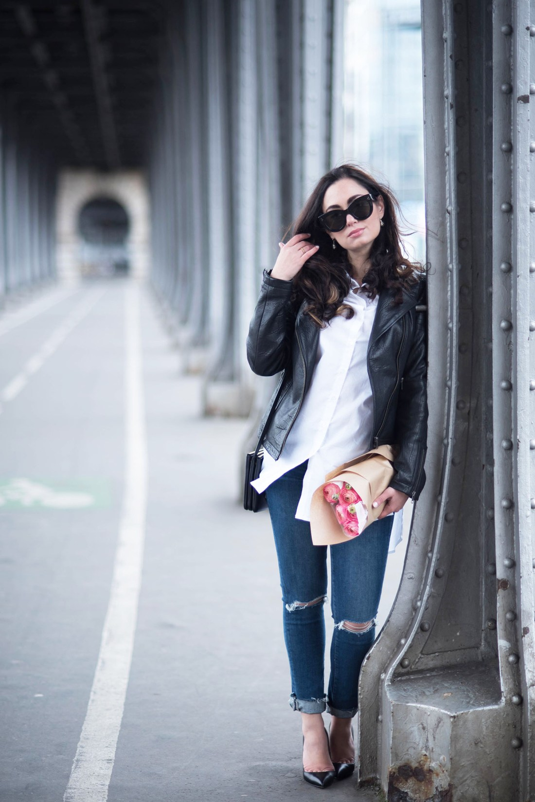 Fashion blogger Cee Fardoe of Coco & Vera stands under pont Bir Hakim in Paris wearing a Marled blouse and Celine Audrey sunglasses