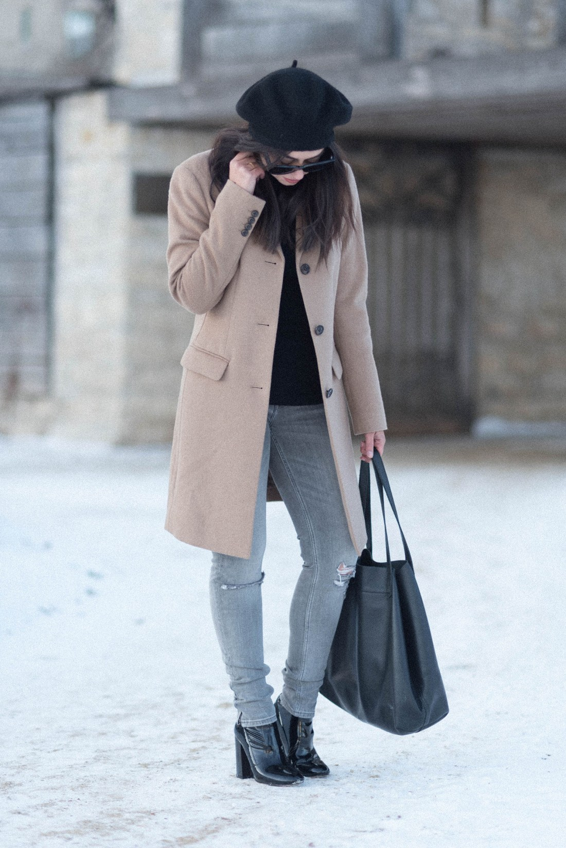 Canadian fashion blogger Cee Fardoe of Coco & Vera wearings a Uniqlo camel coat and Zara grey jeans at Fort Garry in Winnipeg