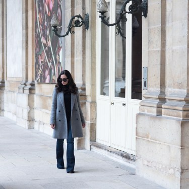 Fashion blogger Cee Fardoe of Coco & Vera walks through les Archives Nationales in Paris wearing Mavi flared jeans and Celine Audrey sunglasses