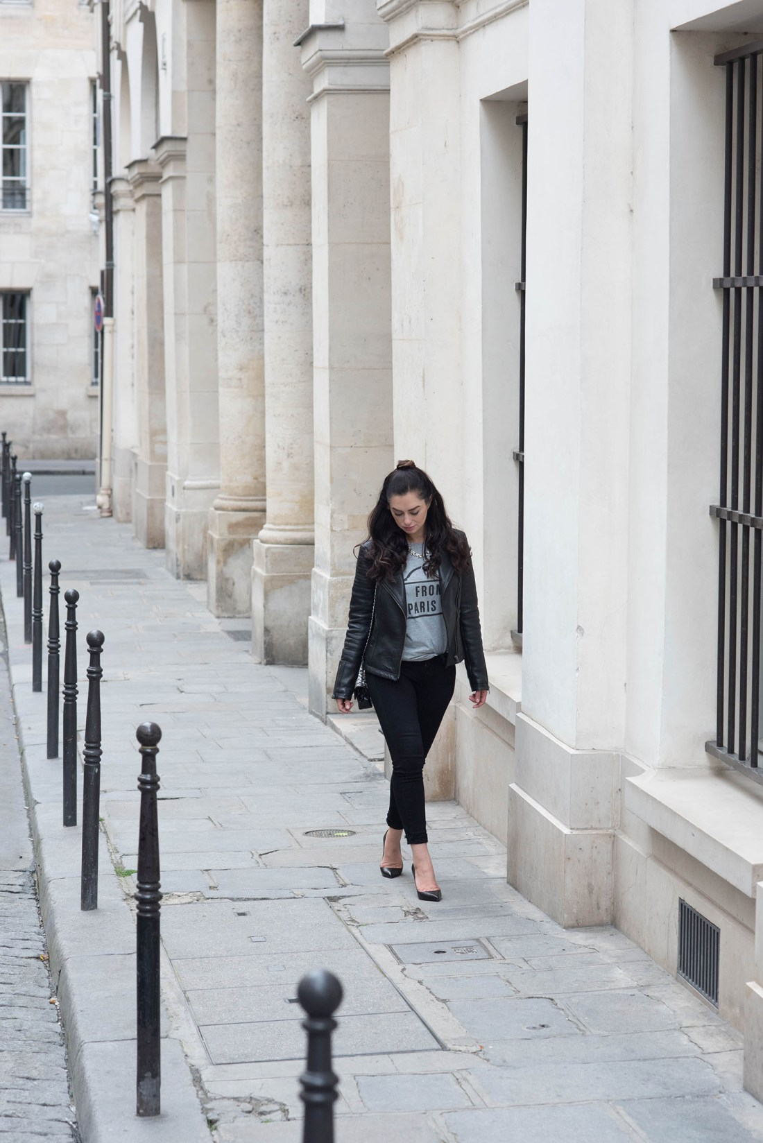 Canadian fashion blogger Cee Fardoe of Coco & Vera walks outside the Palais Royal wearing Paige jeans and Christian Louboutin Pigalle pumps
