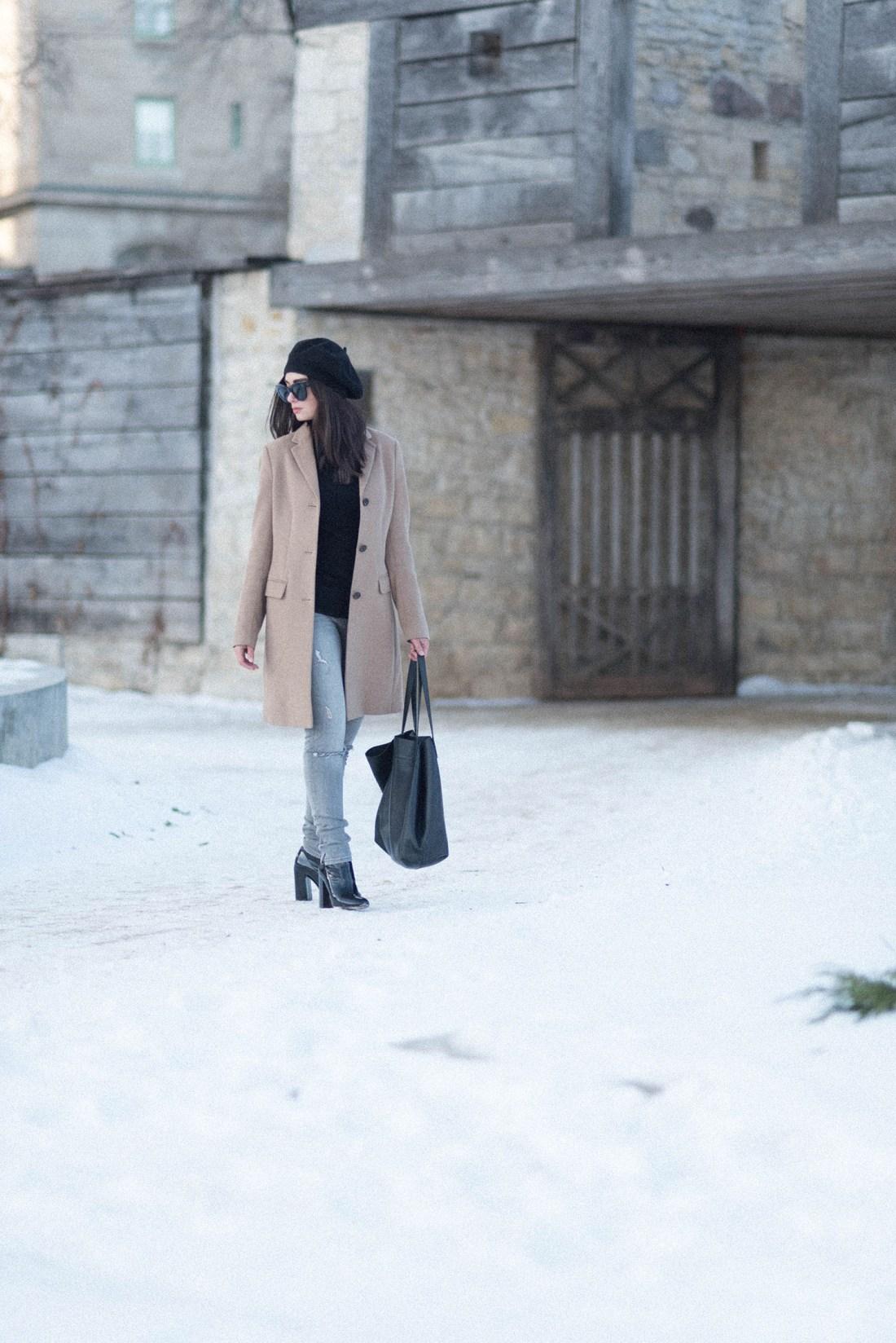 Winnipeg fashion blogger Cee Fardoe of Coco & Vera walks outside Fort Garry wearing a Uniqlo camel coat and an Anthropologie beret