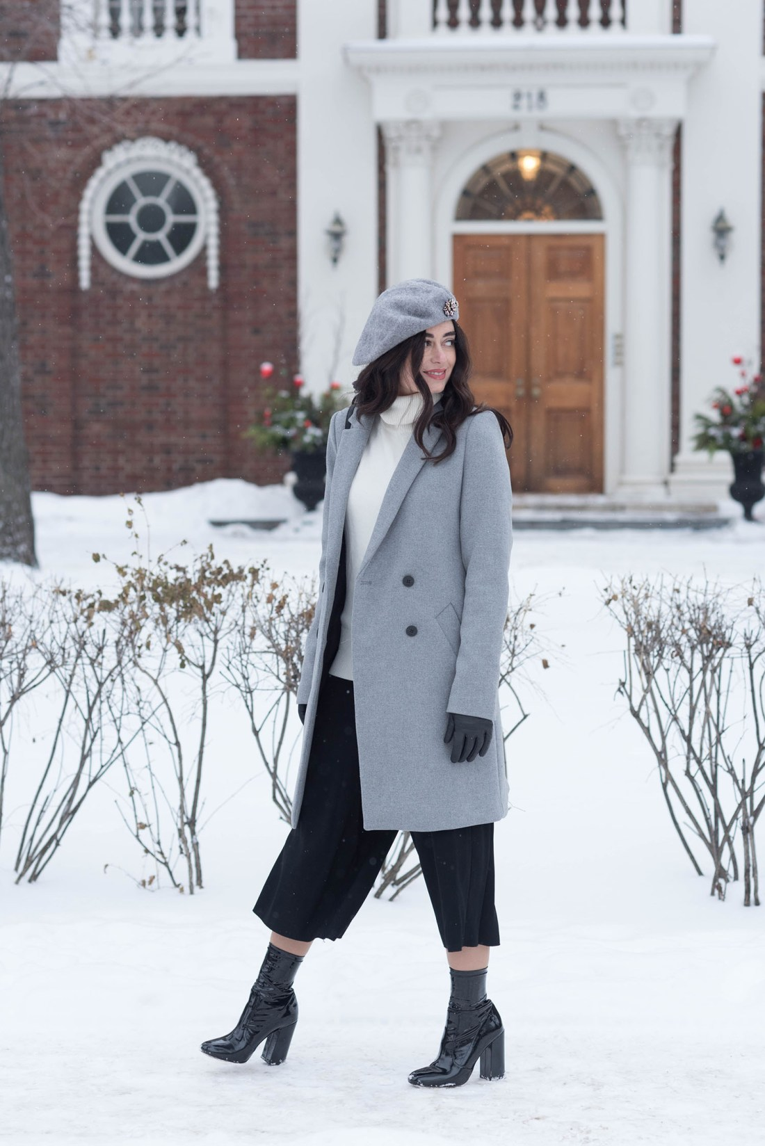 Fashion blogger Cee Fardoe of Coco & Vera walks through the winter snow wearing a Zara coat and Aritzia black culottes