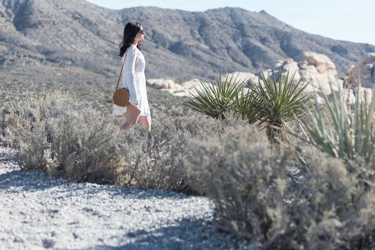 Winnipeg fashion blogger Cee Fardoe of Coco & Vera walks at Red Rock Canyon in Nevada wearing a Tobi dress and carrying a rattan bag
