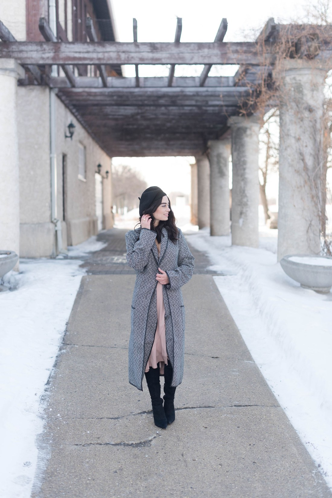 Fashion blogger Cee Fardoe stands outside the Assiniboine Park Pavilion wearing a Lovers + Friends coat and Aldo over the knee boots