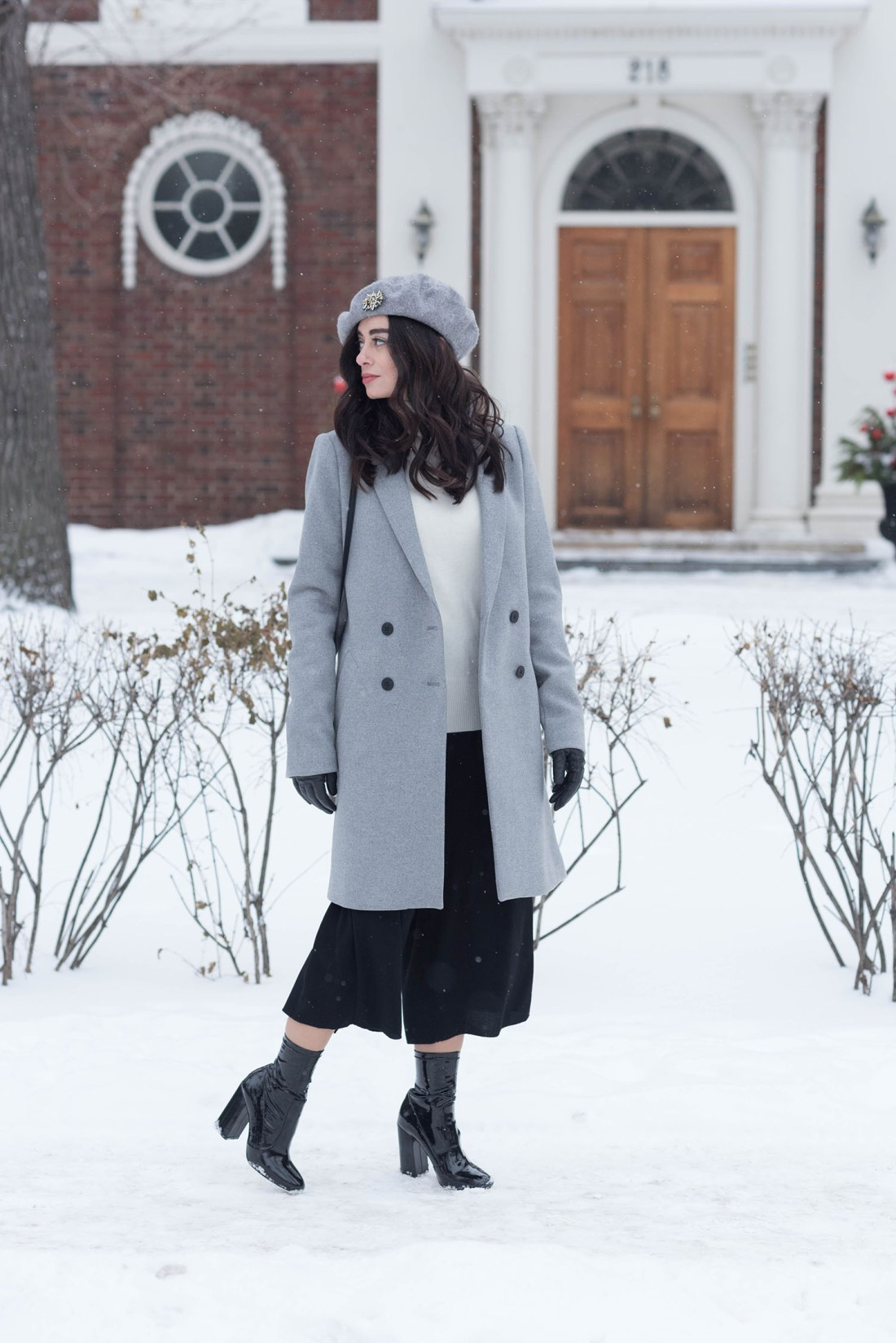Fashion blogger Cee Fardoe of Coco & Vera walks down Roslyn Road in Winnipeg on a snowy day, wearing a grey Zara coat and Raye patent boots