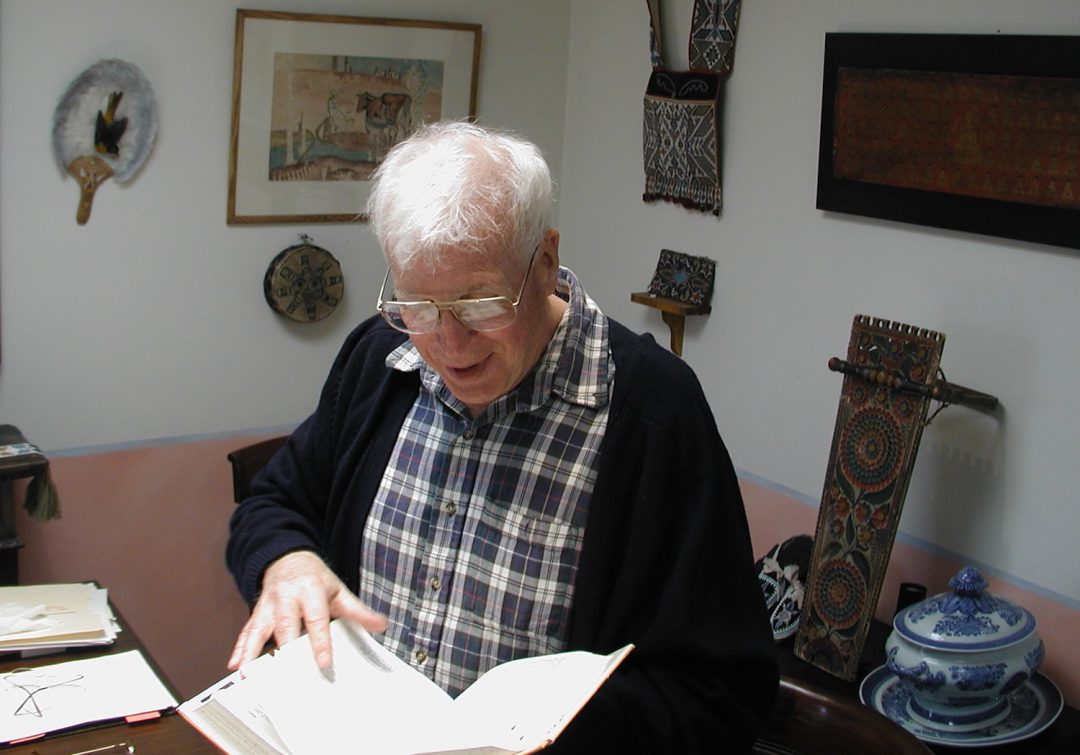 Ted Coe studying in his dining room