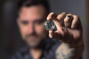 person-holding-silver-bitcoin-coin
