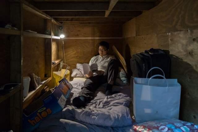 homem lendo em seu pequeno quarto