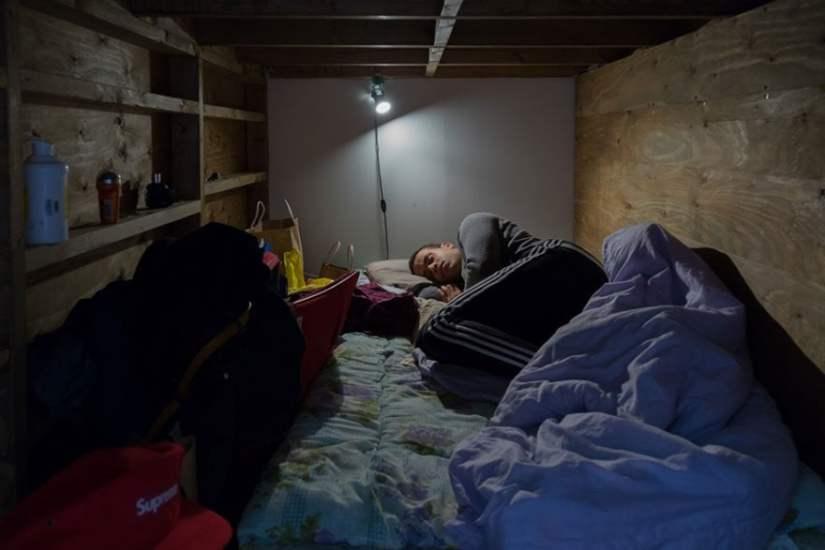 homem dormindo em espaço pequeno