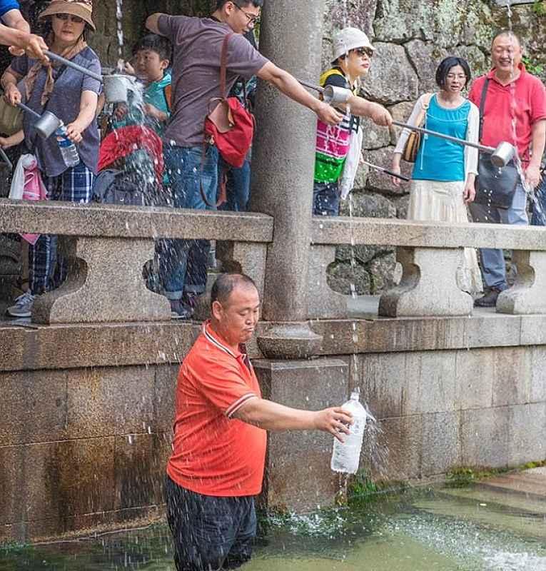 Turista na fonte do templo Kiyomizu-dera