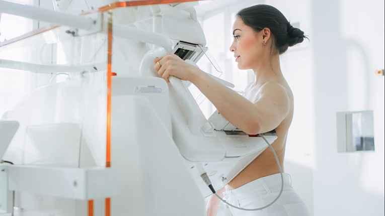 Mulher usando máquina de mamografia