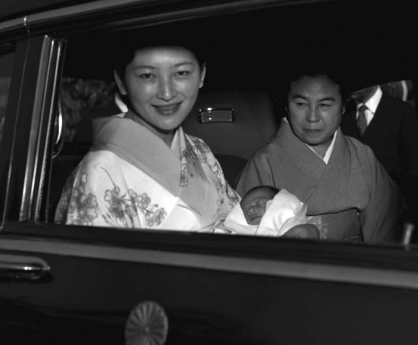 Michiko com Naruhito em seus braçoc