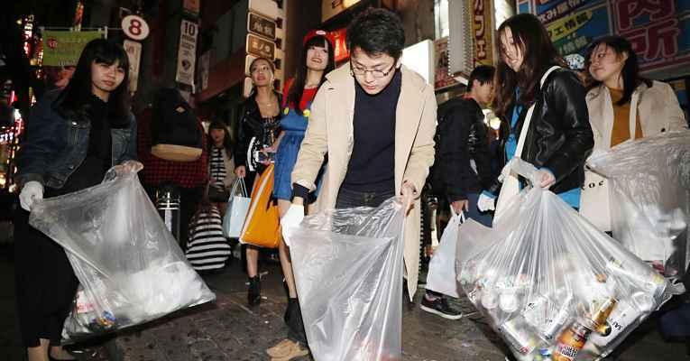 Pessoas recolhendo lixo na rua de Shibuya