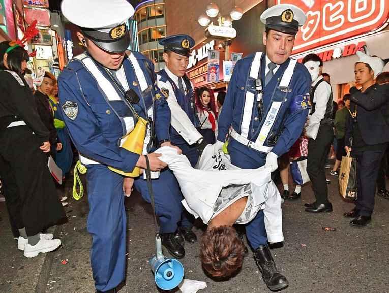 Policiais em Shibuya levando suspeito