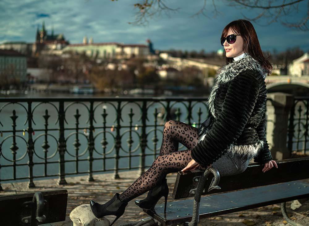 Regina v černých silonkách na lavičce nábřeží Vltavy Hradčany