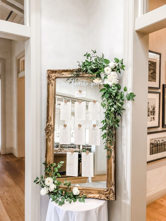 Vintage Mirror Covered in Greenery for Wedding Seating Chart