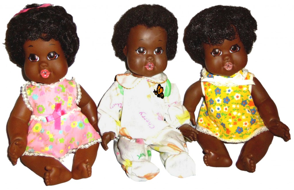 "Top: Jillian Knowles, Samantha's younger sister, sits with their doll collection from childhood in a still from ""Why Do You Have Black Dolls?"" Above: Three Baby Nancys, the first doll produced by Shindana Toy Company, dedicated to making ethnically correct black dolls, in 1968. Photo by Debbie Behan Garrett."