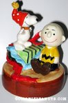 Snoopy standing on gift box with Charlie Brown Music box