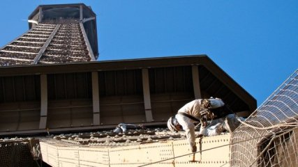 Working on the Eiffel Tower, a painter chips away at the old paint