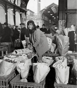 Girl selling flowers at her stand in a pavilion 1968