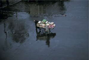 Merchant pulling a cart with food on a rainy day
