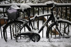 Bike in the snow attached to a railing in front of Jean Sans Peur medieval tower