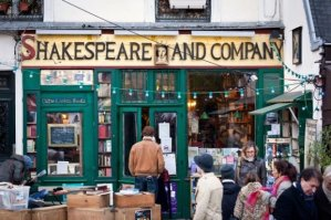View of Shakespeare and Company storefront with people standing out front and someone entering the shop