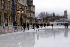 Ice skaters in front of the Paris Hotel de Ville and Notre Dame in the background