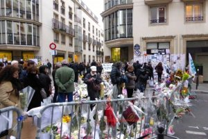 Street leading to Charlie Hebdo's anonymous offices with barricades. Flowers, signs, candles & tributes