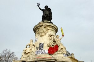 Statue of the Republique with statue Liberté holding a pencil that covers the flame and a red heart at her base.