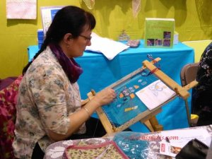 woman working needle point on a frame at aiguille en fete 2015
