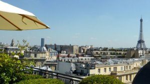 Raphael Hotel terrace view of Eiffel Tower and parasol tip overlooking rooftops