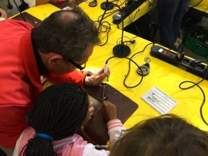 Teaching the kids to assemble a circuit boards Maker Fair