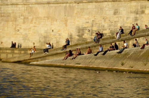 People sitting along the Seine on the Ile-Saint Louis, Quai d'Orléans