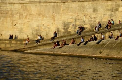 People sitting along the Seine on the Ile-Saint Louis, Quai d'Orléans