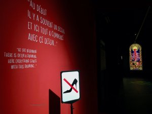 Opening of the exhibit with high heel shoe and red line through it, Louboutin quote on wall