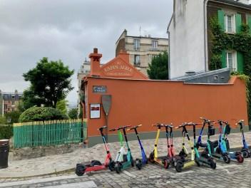 Au Lapin Agile Cabaret Artistique Rue Vincent with colorful trottinettes/scooters